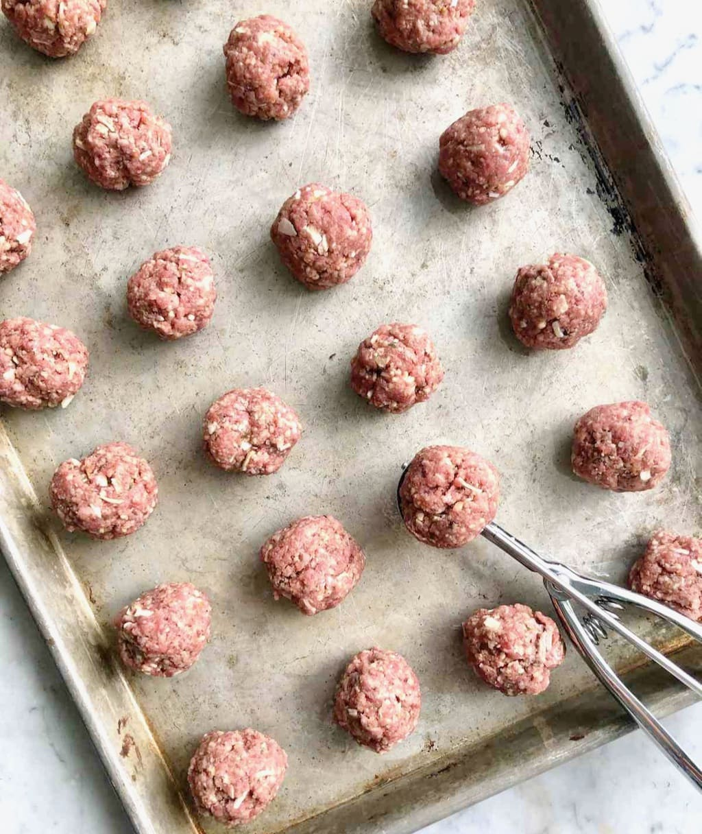 meatballs being rolled out on a sheet pan with a cookie scooper.