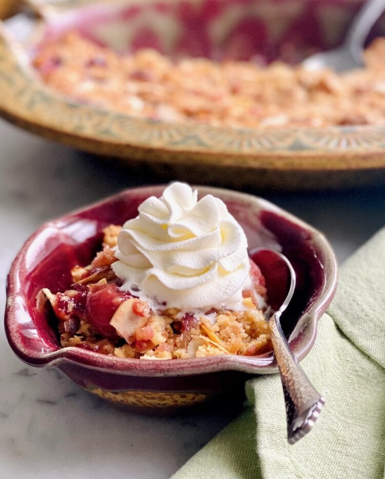 cherry almond cobbler with whipped cream and cobbler in background.