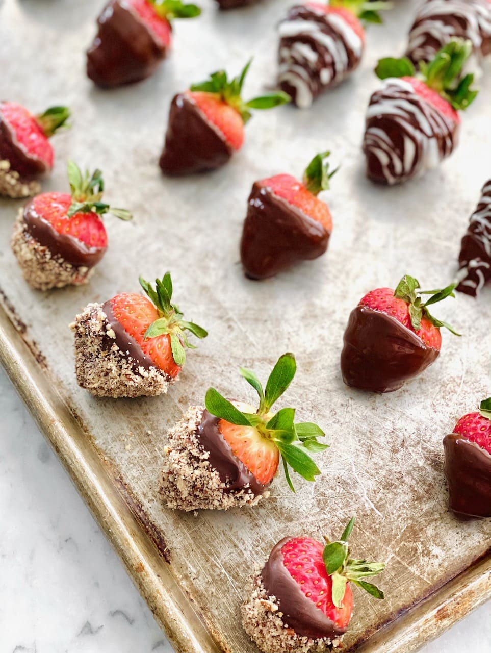 row of dipped strawberries on a sheet pan.