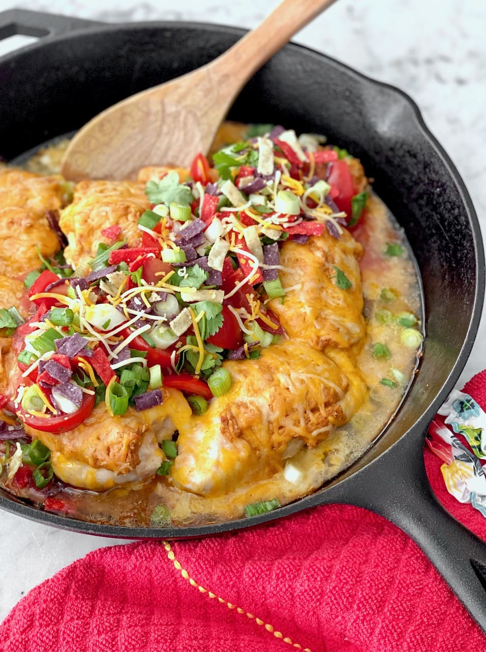 chicken breasts covered with cheese and taco toppings in a cast iron skillet.
