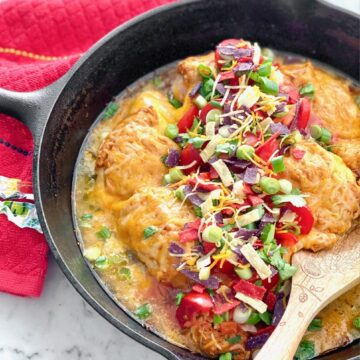 cast iron skillet filled with chicken covered in cheese, tomatoes, onions and cilantro