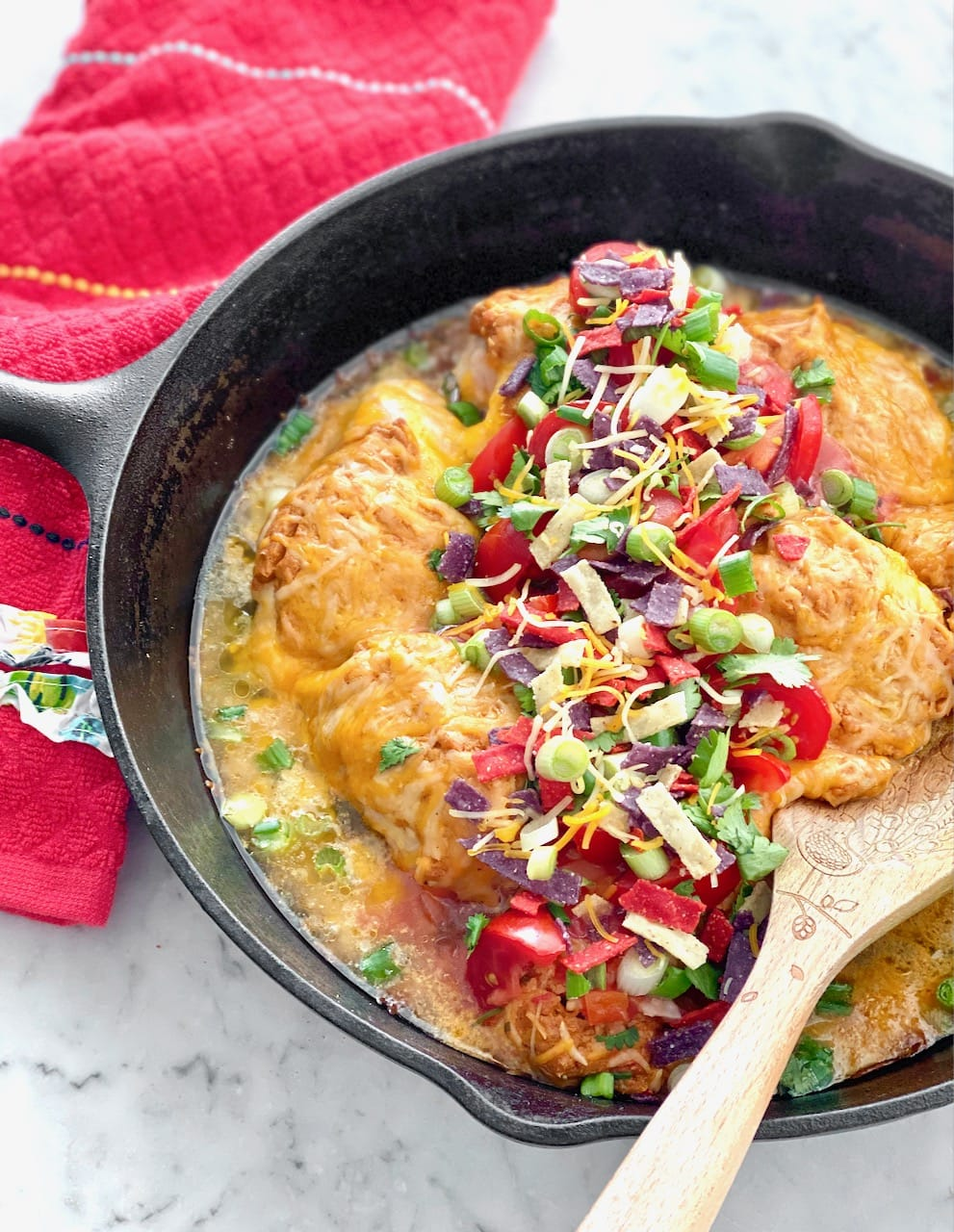 cast iron skillet filled with chicken covered in cheese, tomatoes, onions and cilantro in a cast iron skillet.