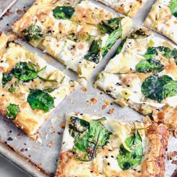 slice of spinach alfredo pizza askew on a sheet pan