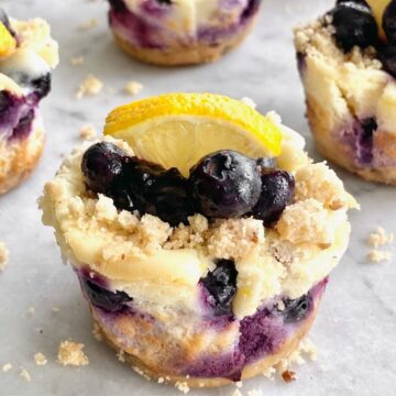 blueberry cheesecake cupcakes with blueberry topping and a lemon slice on top.