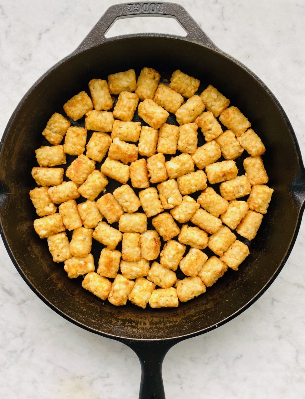 layer of tater tots in a cast iron skillet