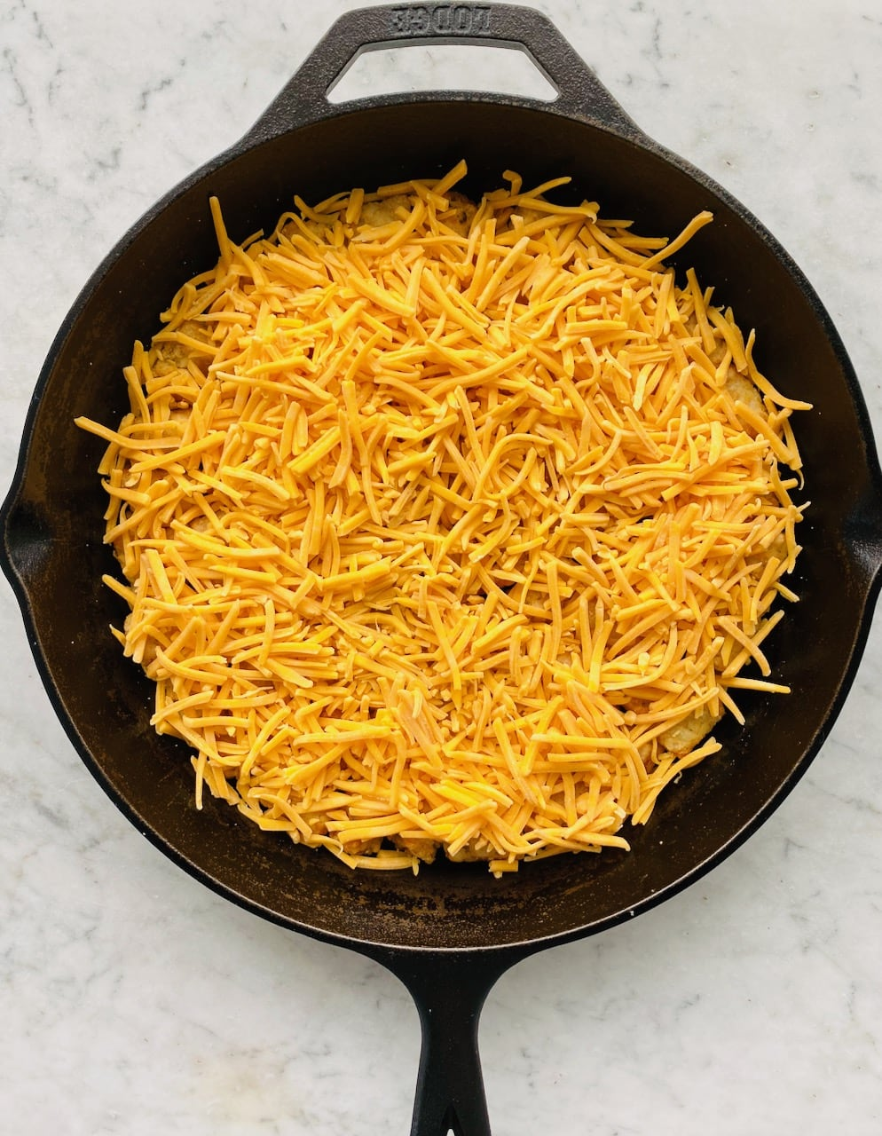layer of cheese in a cast iron skillet