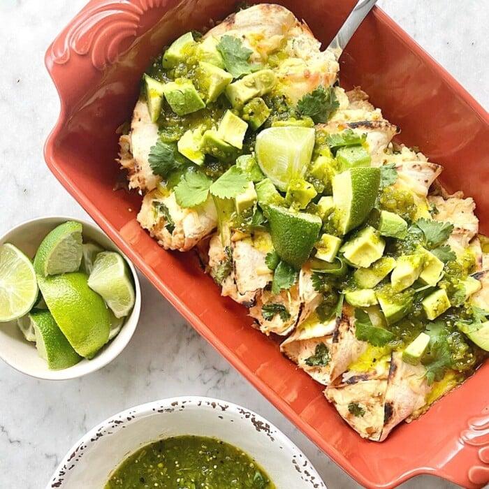 limes, cilantro, salsa verde and avocado top green burritos in an orange dish.