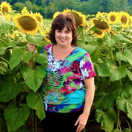 Debi, Author of Quiche My Grits in a field of sunflowers