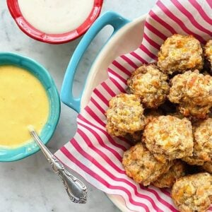 sausage balls in a red lined bowl with dips