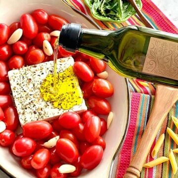 block of feta cheese and tomatoes with seasonings being drizzled with olive oil.