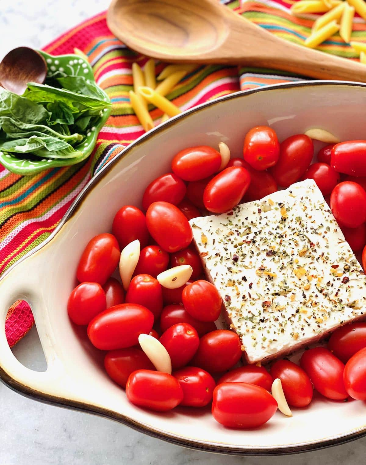 garlic cloves tucked into tomatoes surrounding feta cheese.