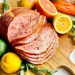 spiral ham glazed with brown sugar and mustard on a cutting board with fruit.