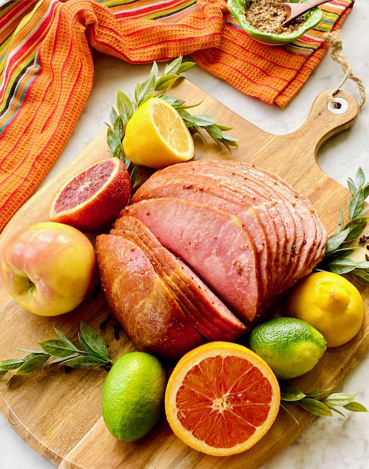 ham surrounded by lemons, oranges, apples and limes.
