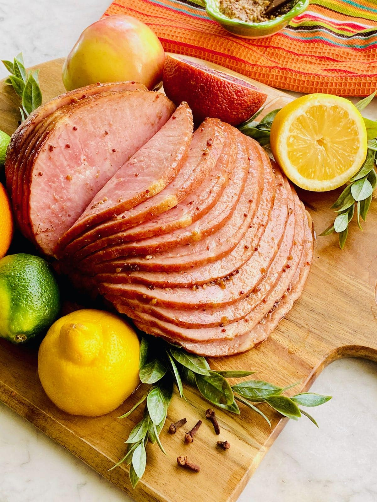 ham with fruit on a wooden board.