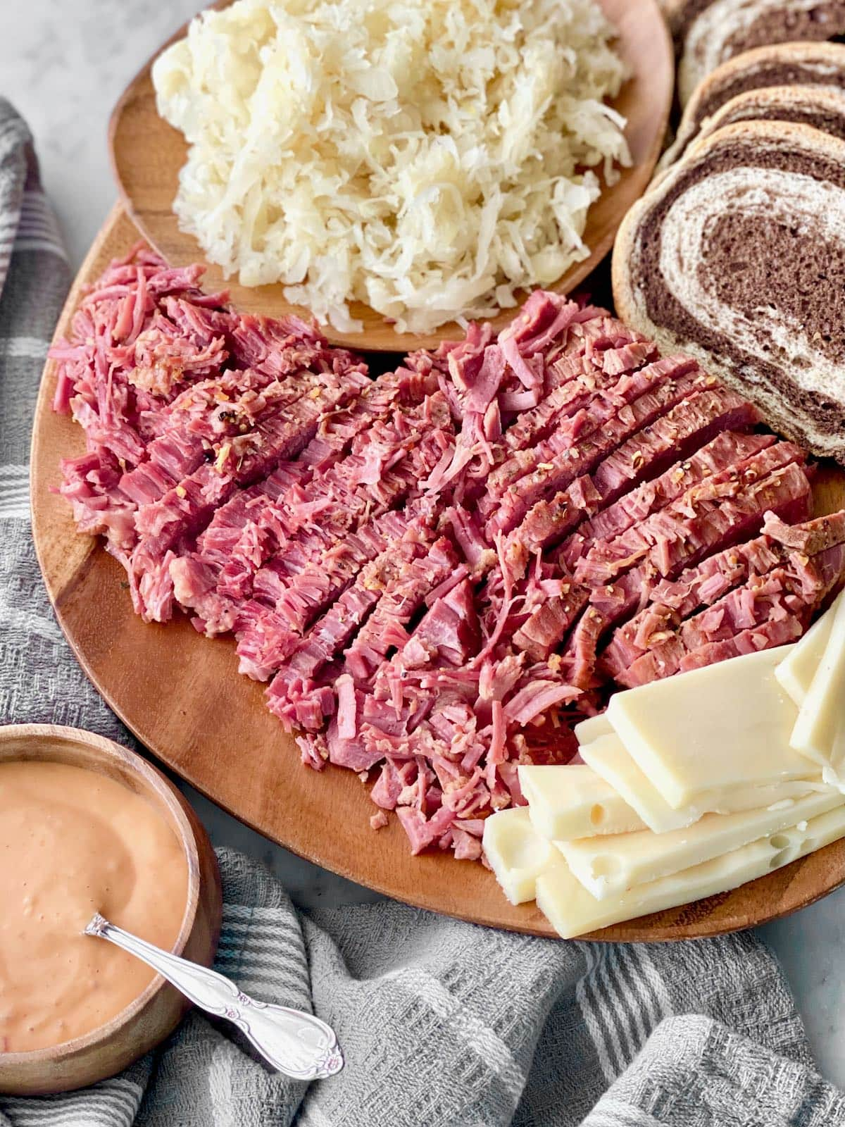 corned beef, sauerkraut, marbled rye, swiss cheese and Russian dressing on a platter.