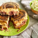 corned beef reuben made from scratch stacked on a green plate.