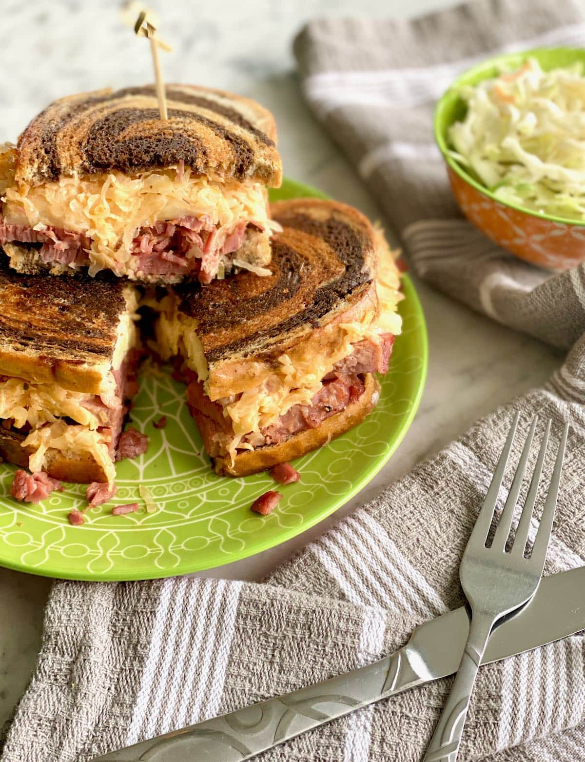 corned beef reuben sandwich with a side of slaw.
