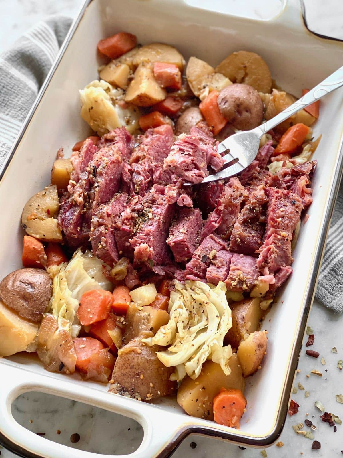 point cut corned beef brisket with cabbage, potatoes and carrots in a baking dish.