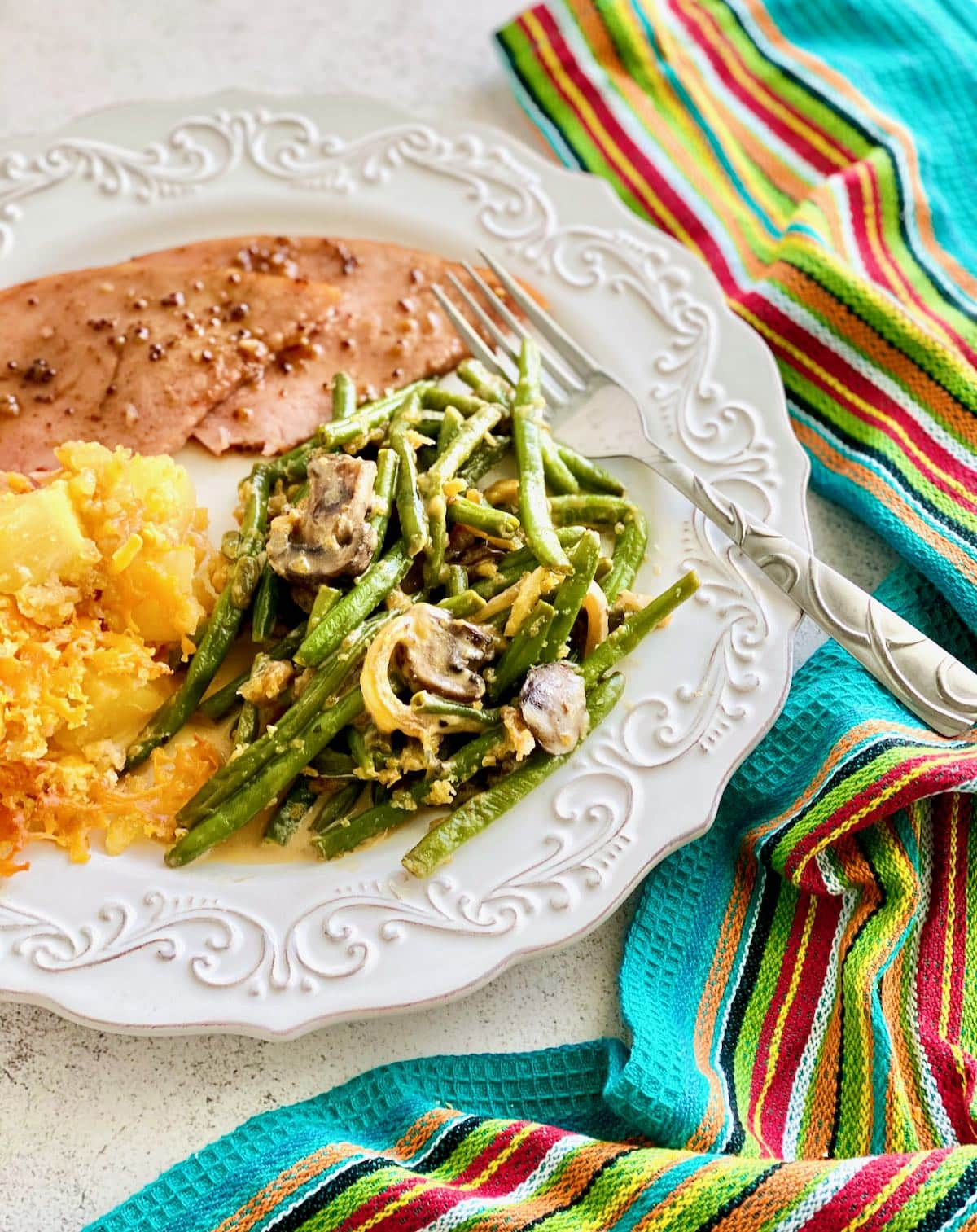 white plate with ham, green beans and pineapple casserole.