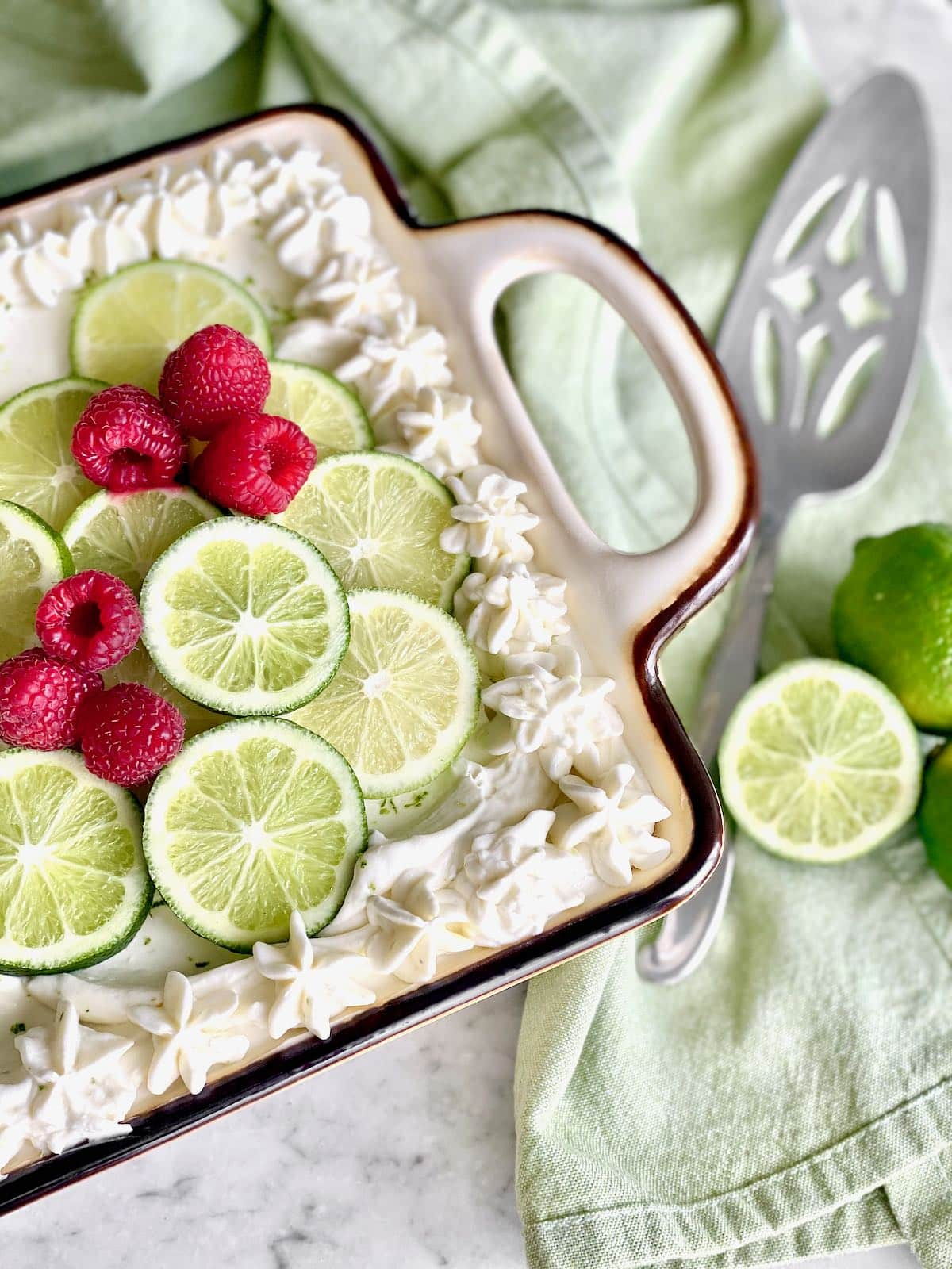 cake with a server and limes on the right side.