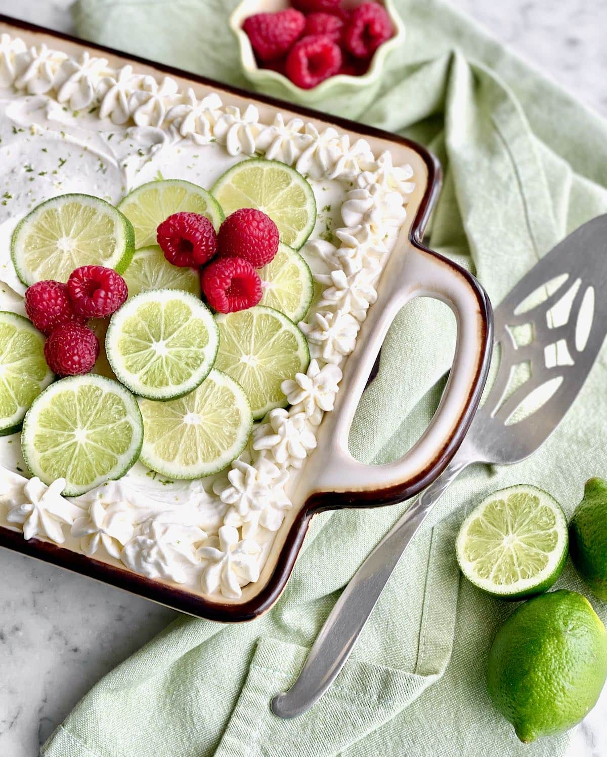 cake in a baking dish with green towel wrapped around the side.