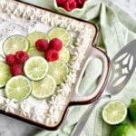 key lime poke cake with lime spices and raspberries on top.