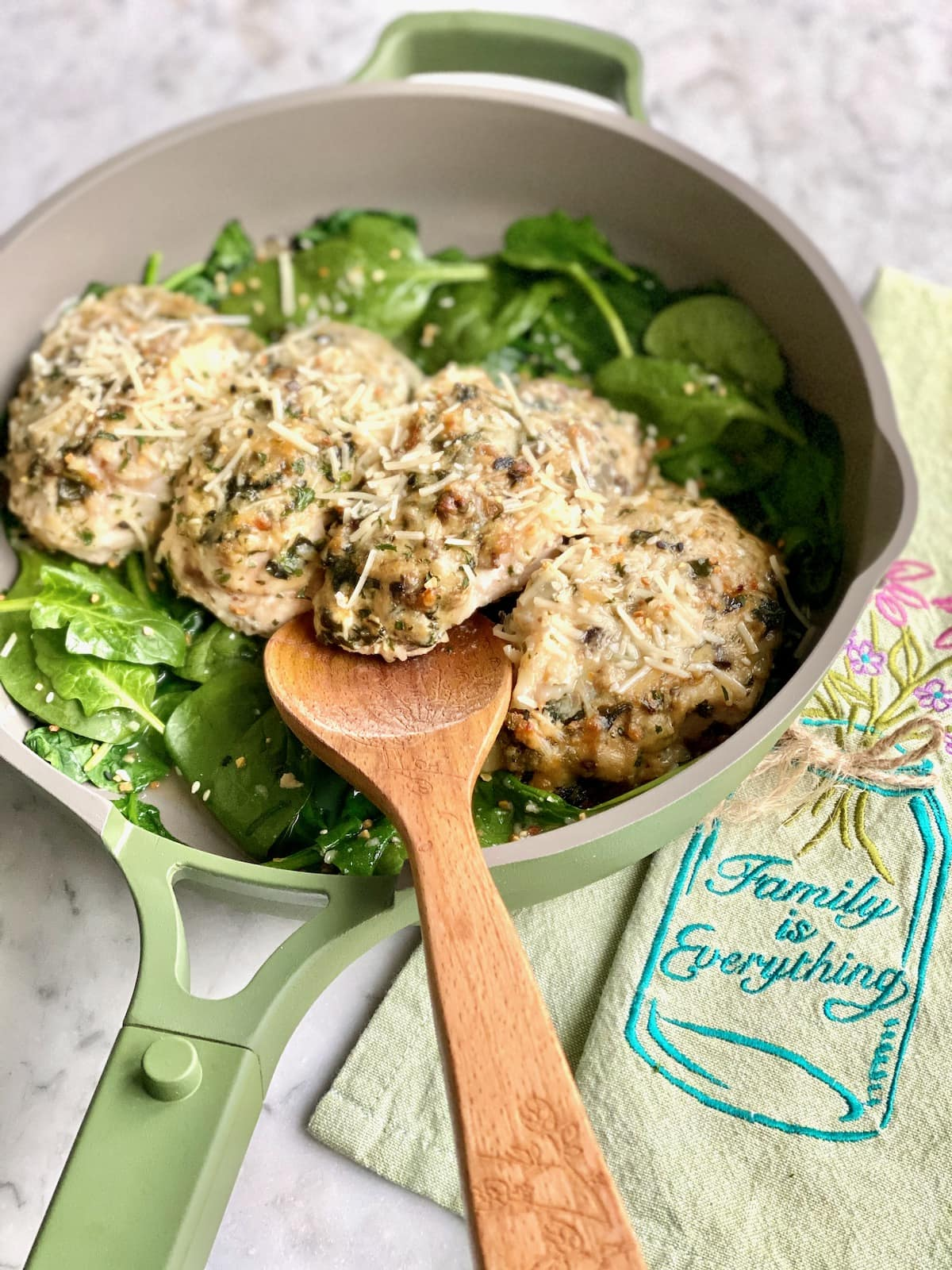 chicken breasts in a green skillet stuffed with cheese.