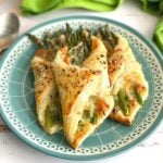 asparagus bundles wrapped in puff pastry on a teal plate.