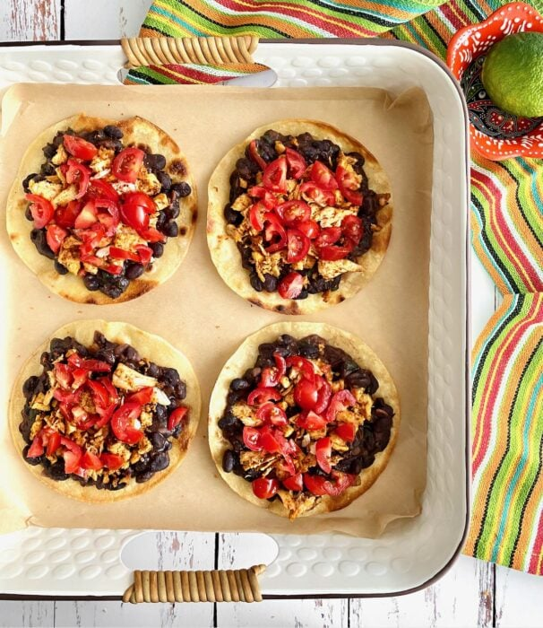tortillas layered with black beans, chicken and tomatoes.