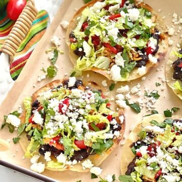 chicken tostadas topped with beans, chicken, lettuce, tomatoes and cheese.