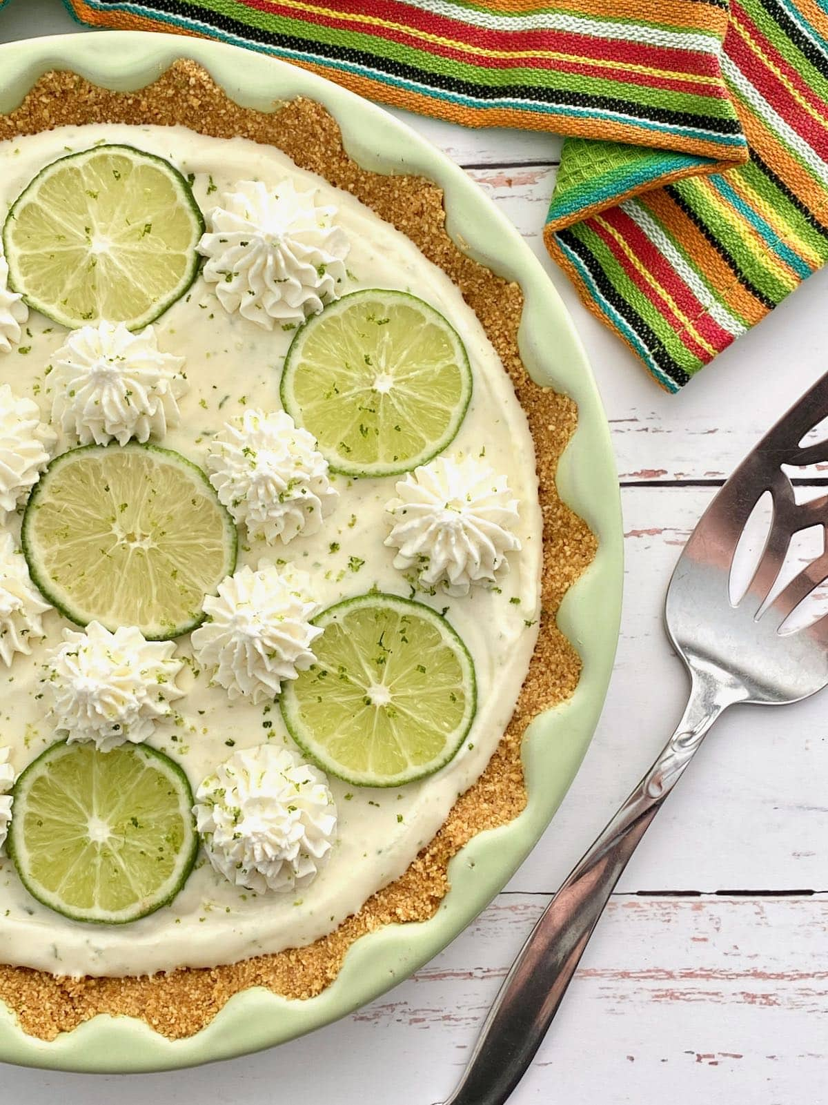 side view of key lime pie with server beside it.