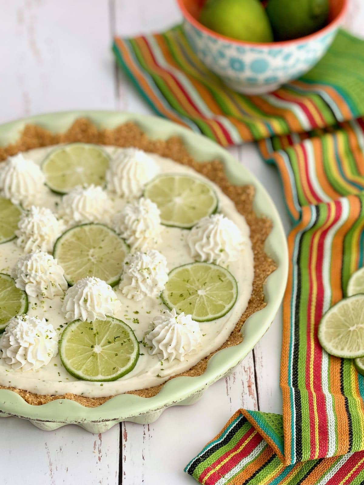 key lime pie decorated with whipped cream and limes.