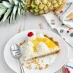 slice of pineapple pie on a white plate with pineapple in background.