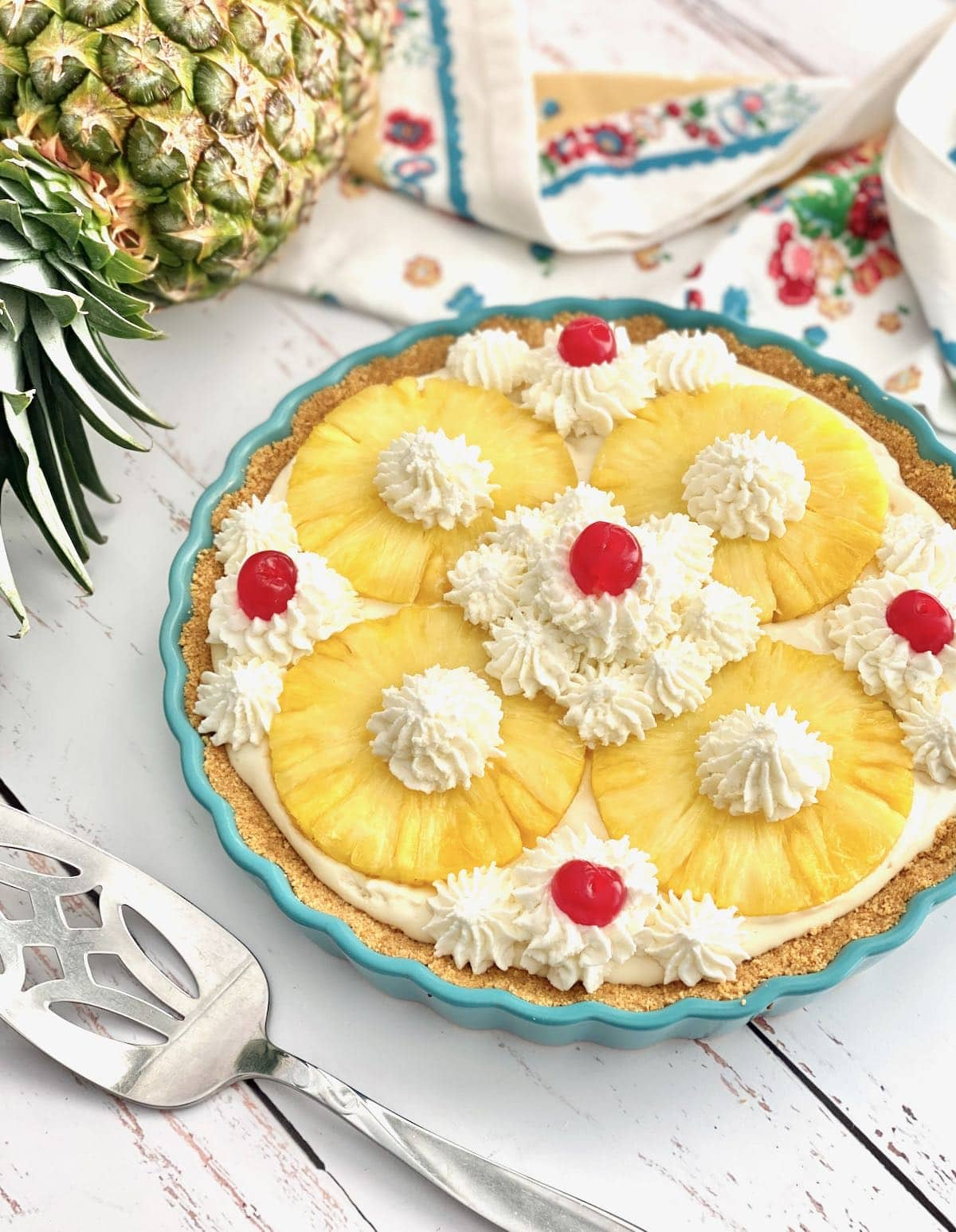 pineapple pie in a blue pie plate on a white washed background.