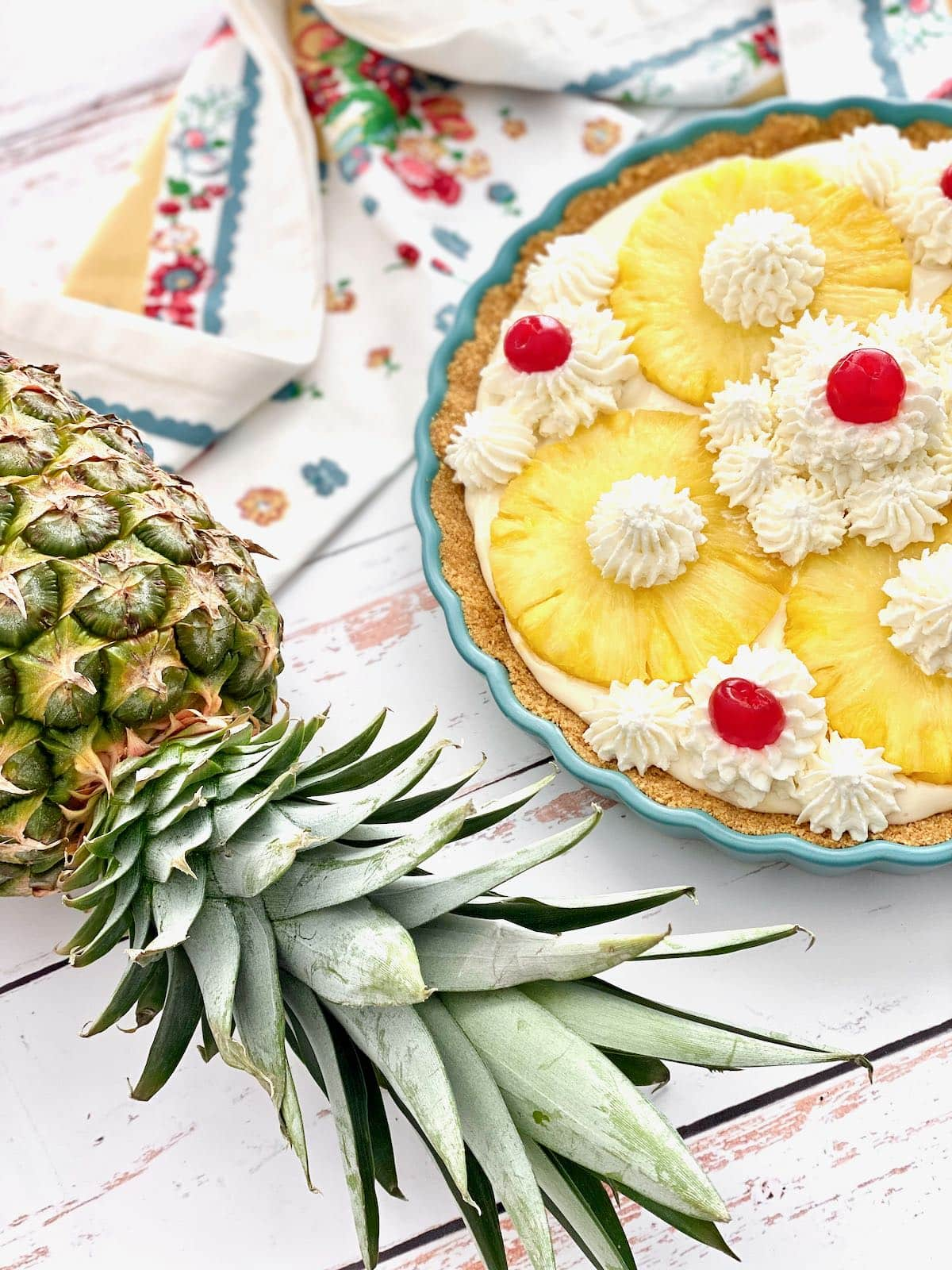 a fresh pineapple laying beside a whole pineapple pie.
