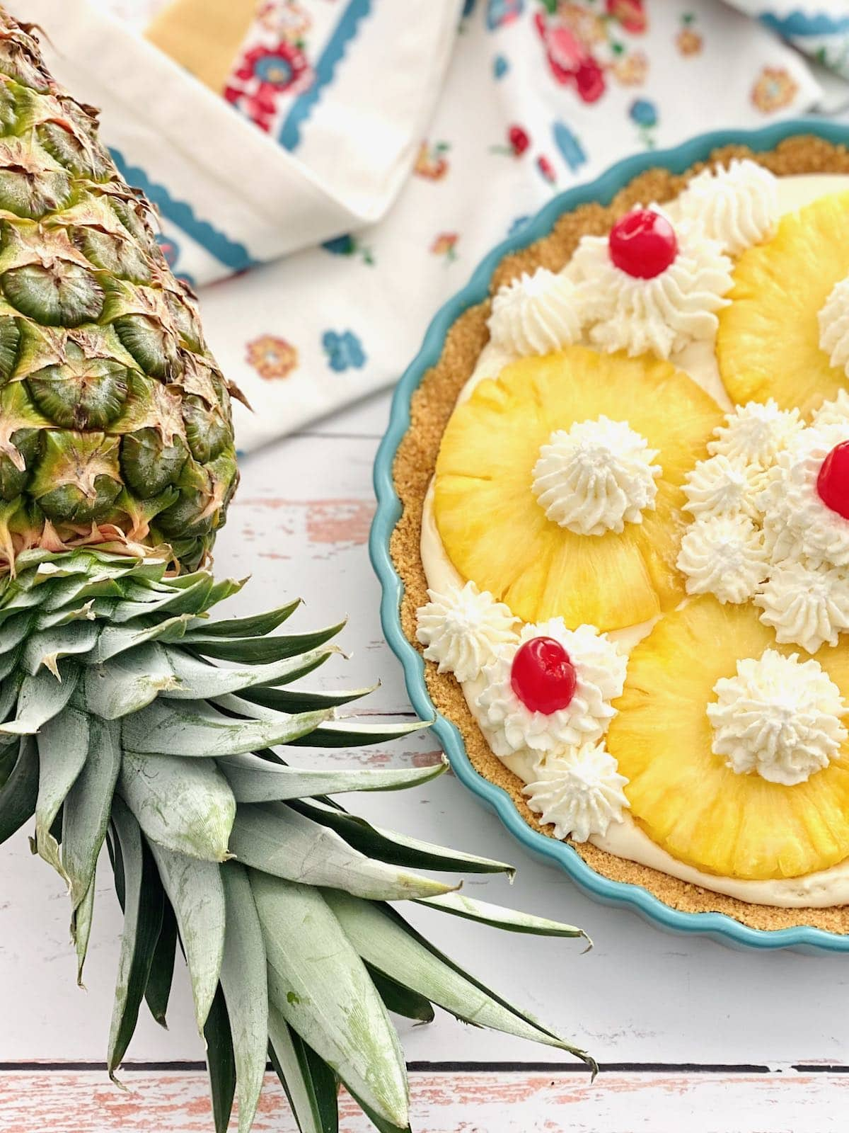 pineapple pie in a blue pie dish with fresh pineapple rings.