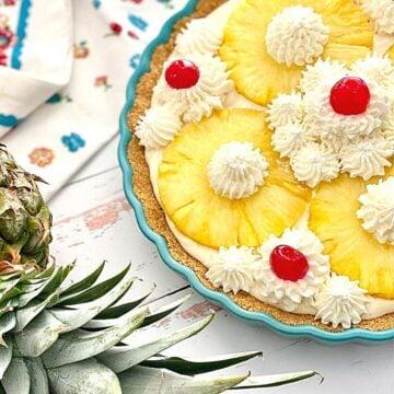 no bake pineapple pie next to a fresh pineapple.