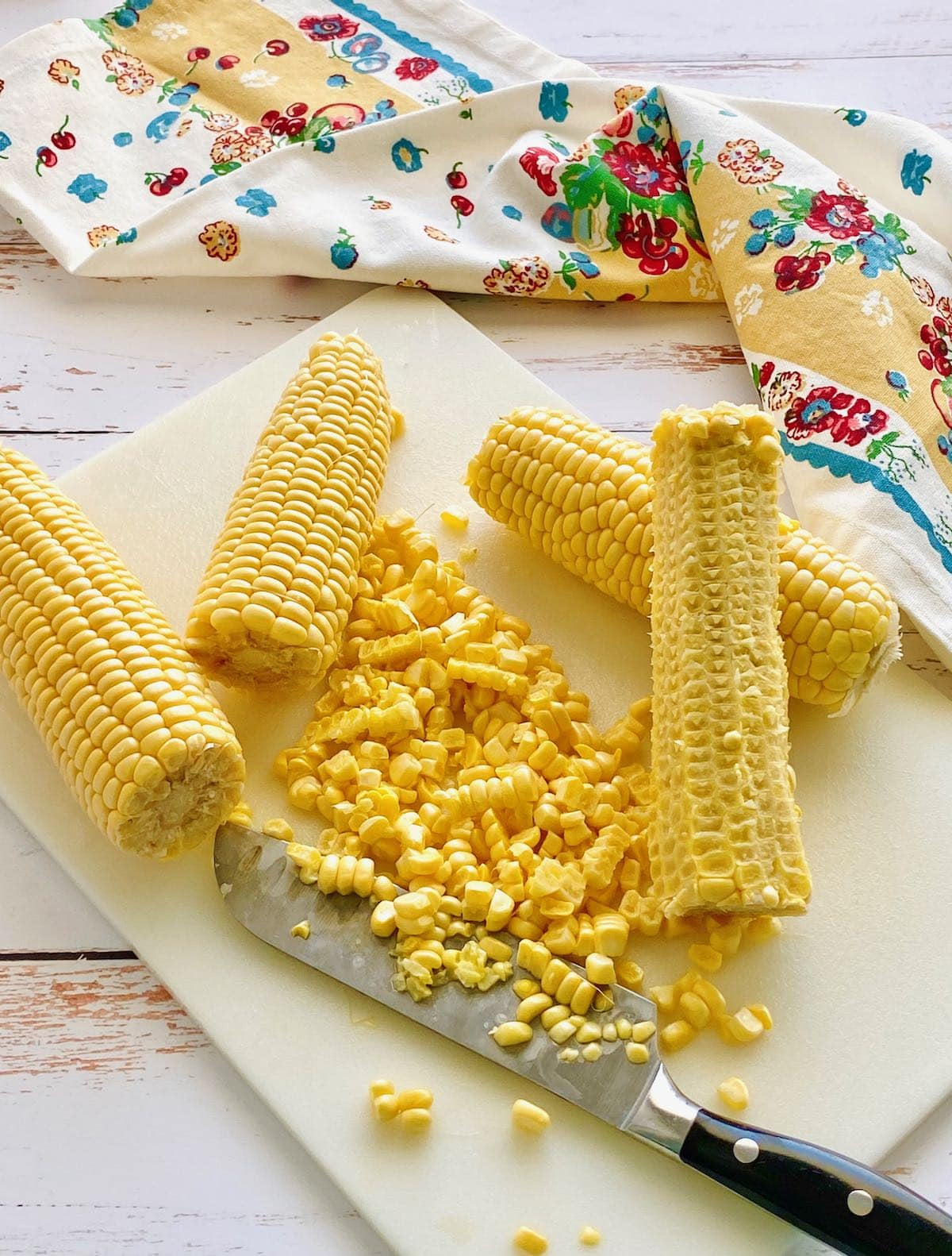 cutting corn off the cob onto a cutting board.