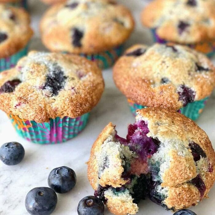 a blueberry muffin bursting open showing the blueberries inside.