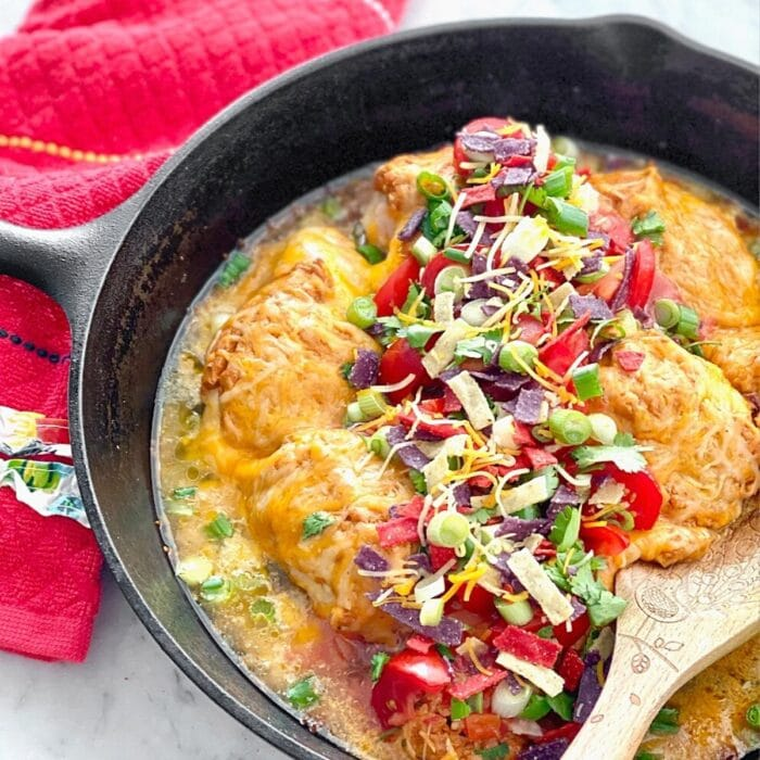 chicken covered with cheese and toppings in a cast iron skillet.