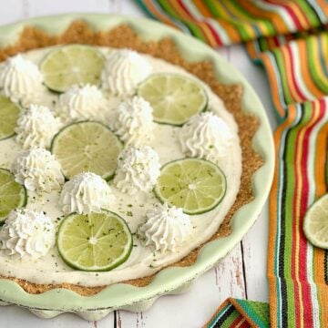 the perfect key lime pie that's no bake and topped with limes and whipped cream.