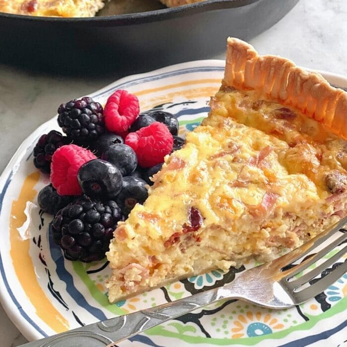 quiche loaded with 3 types of meat on a plate with fruit.