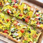 puff pastry loaded with taco toppings on a sheet pan.