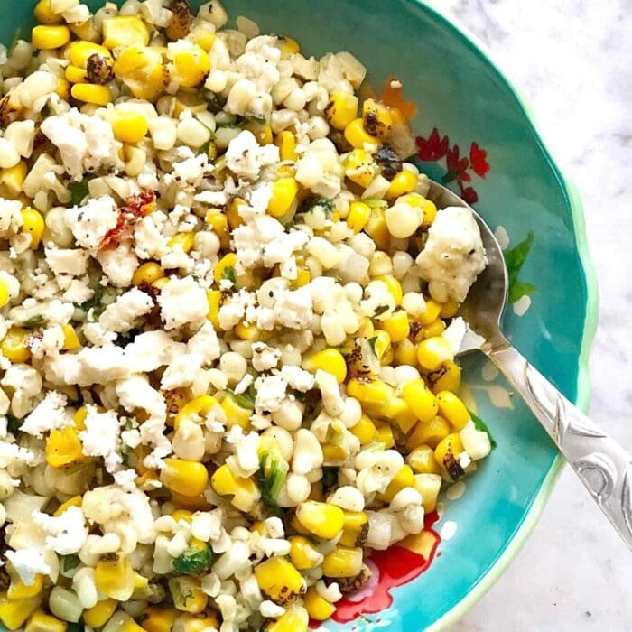 mexican street corn with cheese and cilantro in a blue dish.