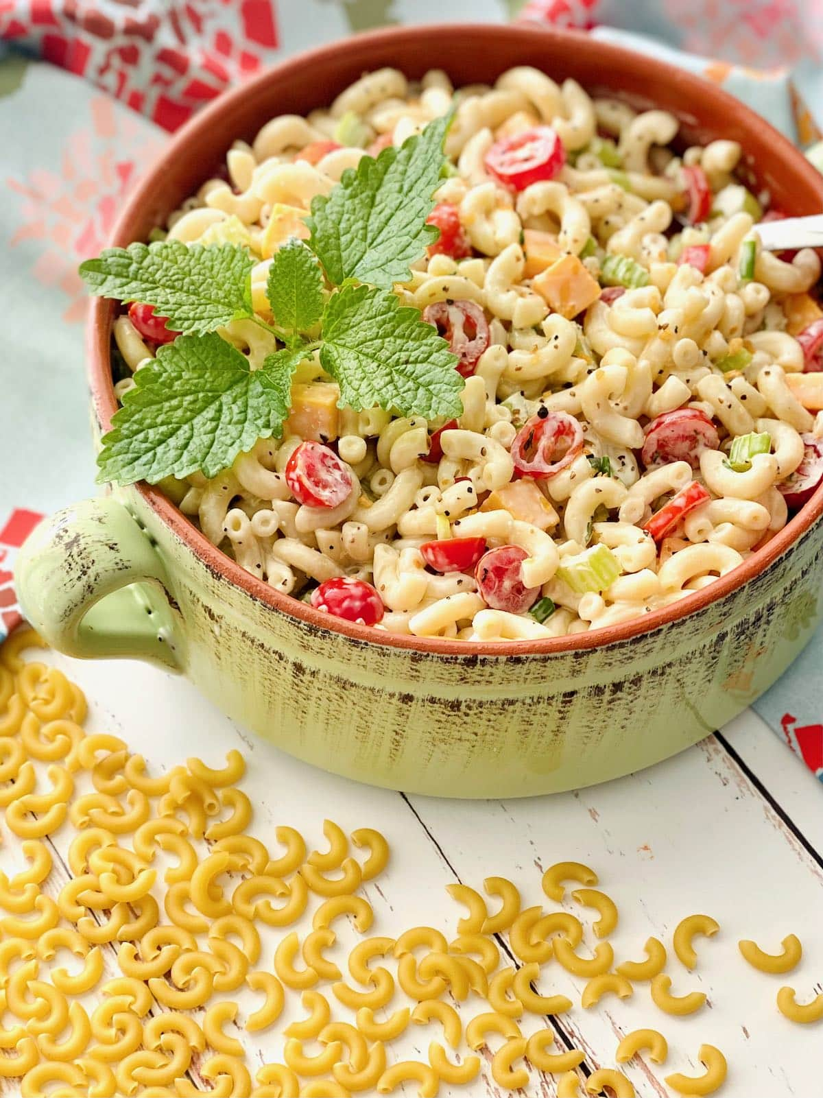 macaroni elbow noodles spilled around a bowl of macaroni salad.