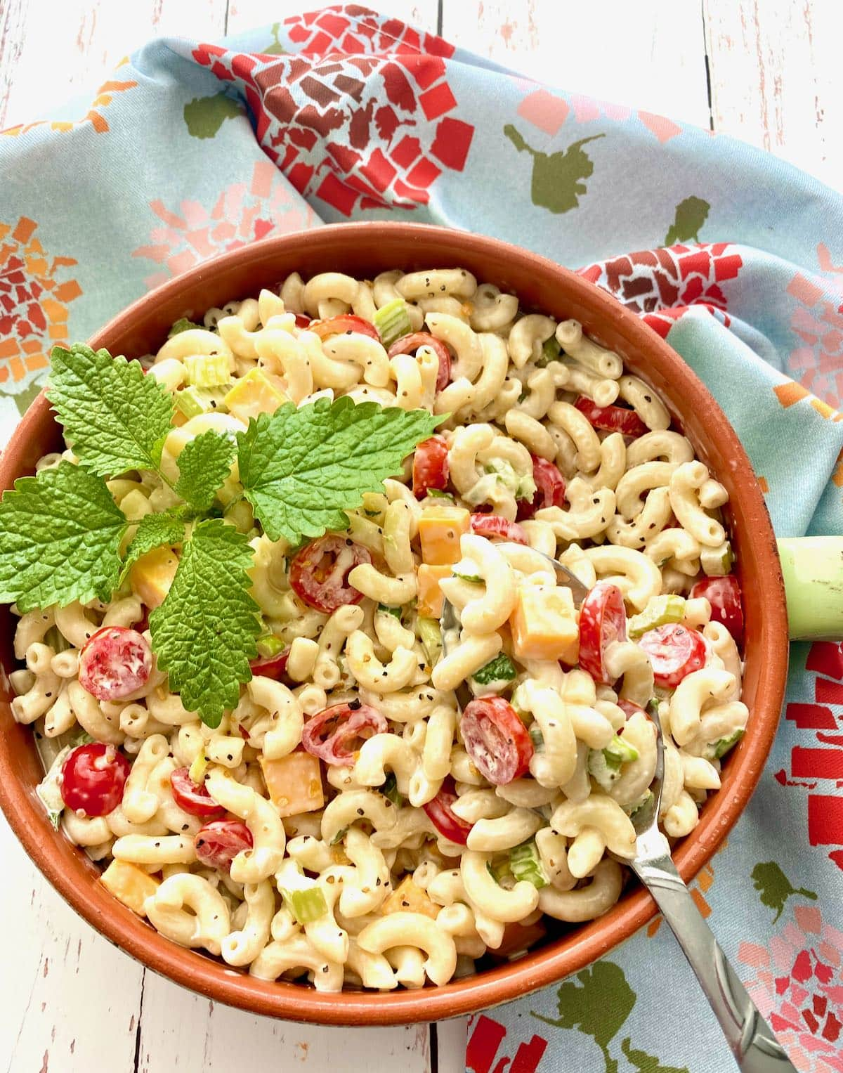 spoon lifting up macaroni salad out of a crock.