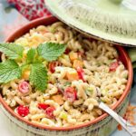 a green dish filled with macaroni salad.
