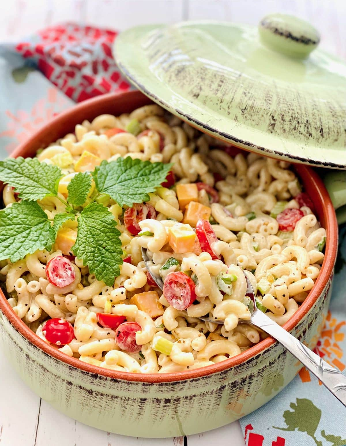 a green dish filled with southern macaroni salad.