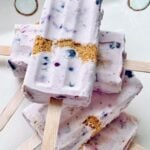 blueberry cheesecake popsicles stacked and staggered on a plate.