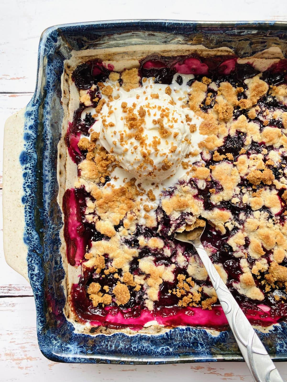 scoop of vanilla ice cream on top of blueberry cobbler.